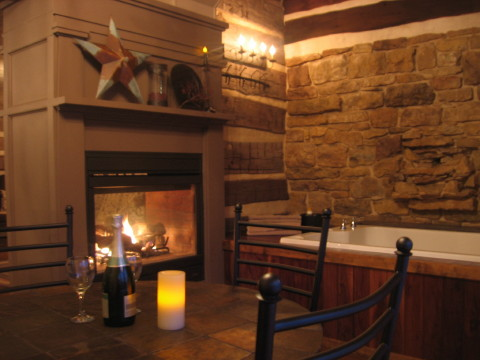 The Back Again Log Cabin Guest House has a gas fireplace and whirlpool for two in the rock room. Ample space with a table and four chairs entices you to come back again.