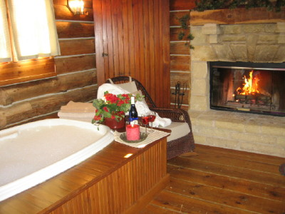 Cabin Life guest house has a whirlpool for two next to the wood burning fireplace